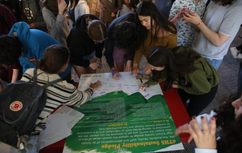 Students sign a sustainablility pledge to be more environmentally friendly in a school-wide effort to combat the effects of climate change.